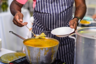 Chef Ricky Moore from the Saltbox Seafood plating his Moqueca (Brazilian fish stew) with fresh North Carolina Seafood.
